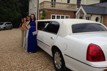 white-limo-with-girls-dressed-up-on-driveway